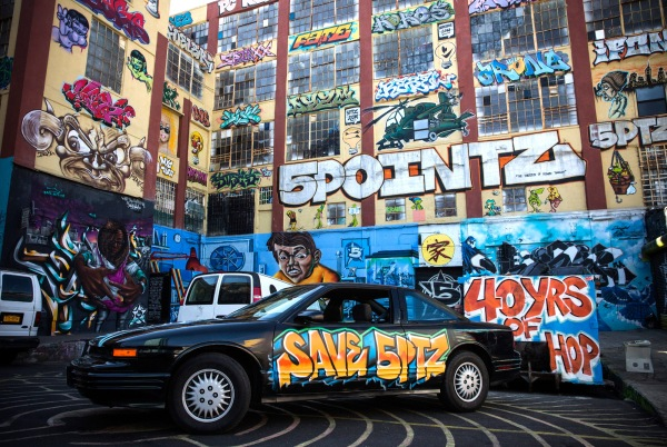 "NEW YORK, NY - OCTOBER 28: A graffiti painted car is parked in front of the 5 Pointz Building, a landmark in the New York graffiti scene that has attracted artists from around the globe, on October 28, 2013 in the Long Island City neighborhood of the Queens borough of New York City. The artists that have been using 5 Pointz to paint for the past two decades are currently in a battle with the building's owners, who want to tear the building down to build apartment high rises worth $400 million. The 5 Pointz artistic community have also called on street artist Banksy who is currently in the midst of a high profile ""month in residence"" series, creating work through out the streets of New York, to weigh in on the battle, though so far the artist has stayed silent. Meres One says he is prepared to chain himself to the building, should demolition move forward. (Photo by Andrew Burton/Getty Images)"